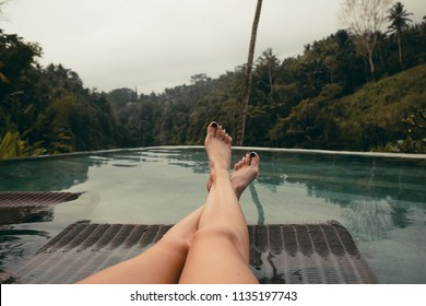 Young woman legs relaxing by pool
