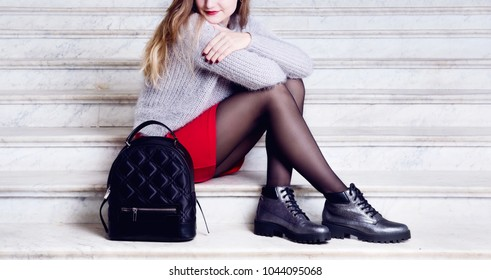 Young woman legs in silver boots with black bagpack. Trendy hipster outfit style. Model sitting on stairs