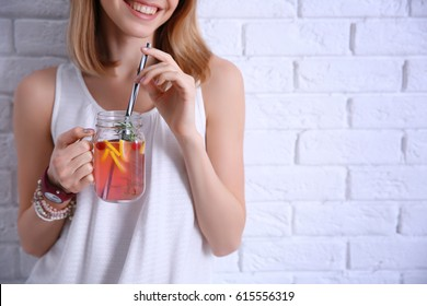 Young woman with lemonade near light brick wall