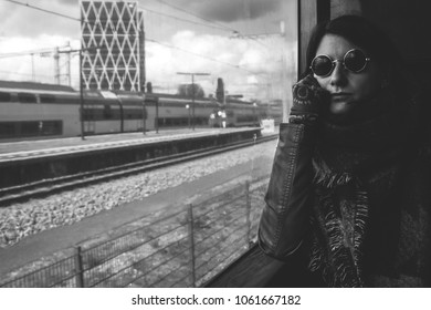 Young woman with lennon sunglasses traveling by train in Amsterdam, black and white portrait photo