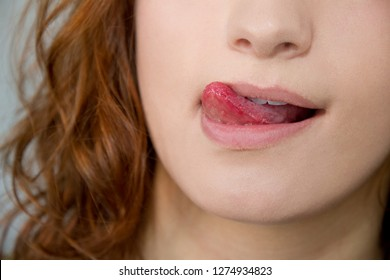 Young woman licking lips