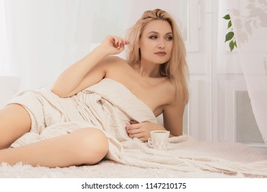Young woman lies in bed with a cup of coffie, looking away.