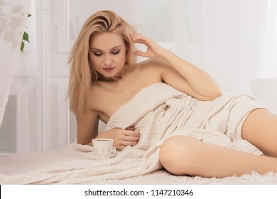 Young woman lies in bed with a cup of coffie.