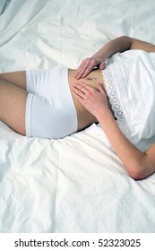 young woman lies on bed with abdominalgia