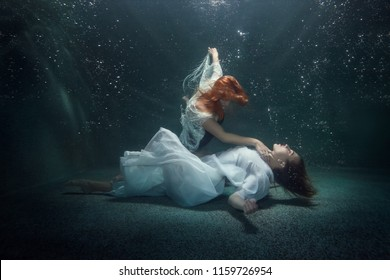 Young woman lies on the bottom under water, another woman holds her hand by the neck.