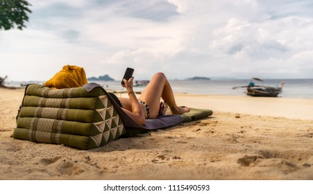 Young woman lies on a dream beach on a towel and plays with her mobile phone