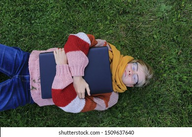 young woman lies on grass with laptop