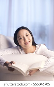 young woman lies on sofa reading book