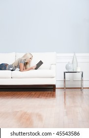Young woman lies on a white sofa in a checkered top and blue jeans while reading a book. Vertical shot.