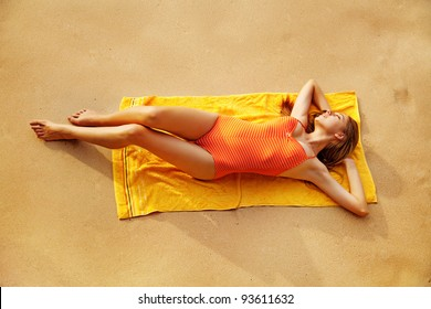 Young woman lies in summer on the beach