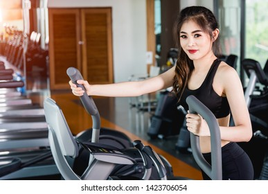 Young woman lifestyle using machine elliptical for cardio workout at fitness gym