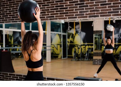 Young woman lifting fitballs in the gym in front of a mirror.