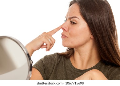 Young woman lifting her nose with her finger on white background