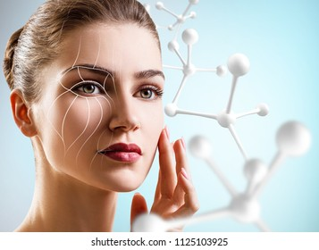 Young woman with lifting lines on face near big white molecule chain.