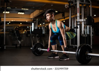 Young woman lifting weights in the gym