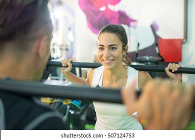 Young woman lifting weights with her male friend.