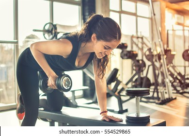 Young woman lifting weights on training class at gym.