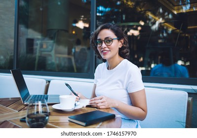 Young woman in light casual clothes wearing eyeglasses and smiling at camera while working on project and sitting at outdoor cafe table