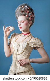Young woman in light corset eagerly looks at a delicious cake over blue background. Updo baroque hairstyle with dry roses.