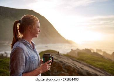 Young woman with light ginger hair and a fresh beauty, standing quietly with a flask of coffee in the early morning, looking out at a picturesque coastline