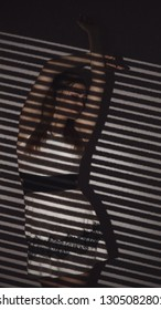 young woman with light pattern of blinds, concept women's emotions and beauty, gobo masks