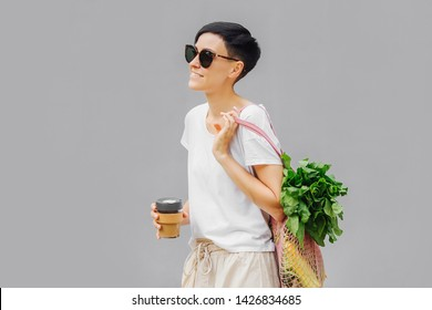 Young woman in light summer clothes with a eco bag of vegetables, greens and reusable coffee mug. Sustainable lifestyle. Eco friendly concept.