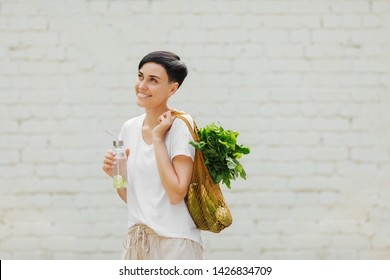 Young woman in light summer clothes with a eco bag of vegetables, greens and reusable water bottle.  Sustainable lifestyle. Eco friendly concept.