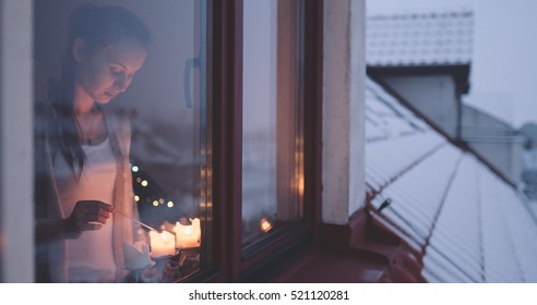 Young Woman lighting Advent Candles on the Window, Winter Cozy Evening. Winter Holidays concept. Christmas Traditions. View from outside the window. Snow-covered house.