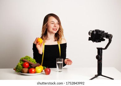 A young woman in lightroom writes a blog on weight loss and healthy eating