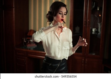 Young woman lights a cigar.She brings flame of burning match to a cigar. Atmosphere of retro.