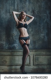 Young woman in lingerie indoors portrait on wall background. Vintage film style colors.