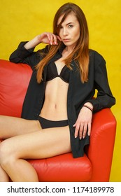 Young woman in lingerie sitting on sofa and thinking