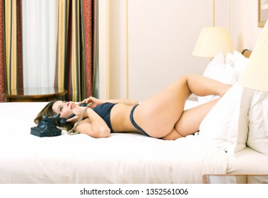 Young woman in lingerie talking at a vintage black phone while lying in bed