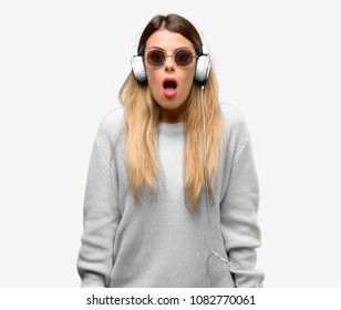 Young woman listen to music with headphone scared in shock, expressing panic and fear