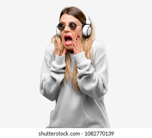 Young woman listen to music with headphone stressful keeping hands on head, terrified in panic, shouting