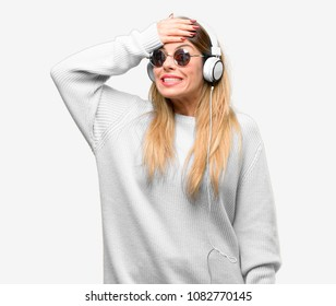 Young woman listen to music with headphone terrified and nervous expressing anxiety and panic gesture, overwhelmed