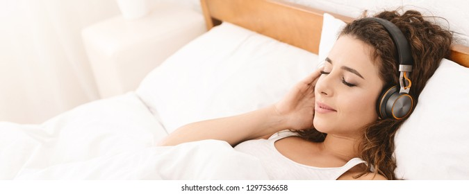 Young woman listening to audiobook in bed, using wireless headphones, panorama, copy space