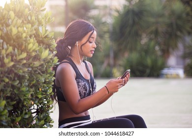 Young woman listening to music before workout
