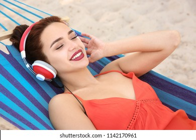 Young woman listening to music in comfortable hammock at seaside