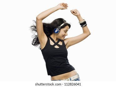 Young woman listening to music and dancing