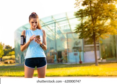 Young woman listening to music with earphones on smart phone app for fitness motivation. Athlete runner in sportswear at the city park