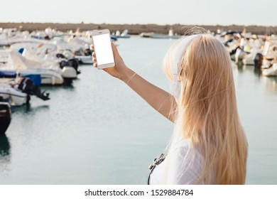 Young woman listening music with headphones using smart phone and walking in a sea port with yachts on background.