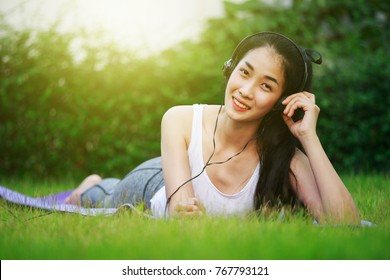 young woman listening to music with headphones and laying on a grass field