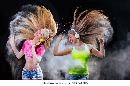 Young woman listening music in headphones in the fog of colors during Holi celebration