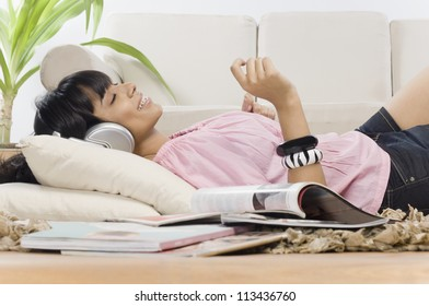 Young woman listening music in a living room