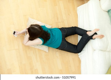 Young woman listening music lying down on the floor at home