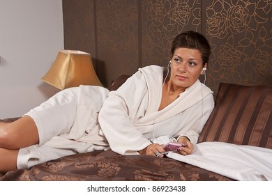 Young woman listening to music lying on a bed