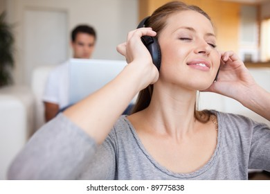 Young woman listening to music with man sitting behind her on the sofa