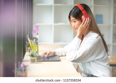 Young woman listening to music in office.