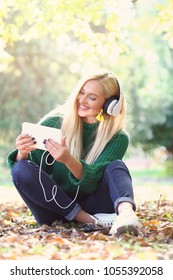 Young woman listening to music on grass outdoors.
